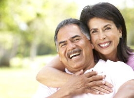 Smiling couple with dental implants in Clinton Township