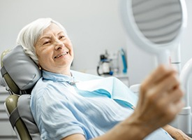 elderly woman admiring her smile in the mirror