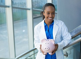 smiling dentist holding a pink piggy bank