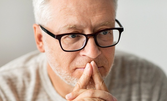 A middle-aged man wearing glasses and thinking about his decision to pursue dental implants in Clinton Township