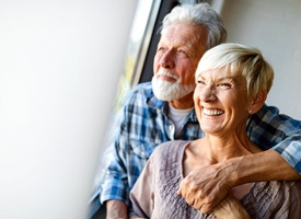 An older couple staring out a window and smiling after receiving their new dental implants