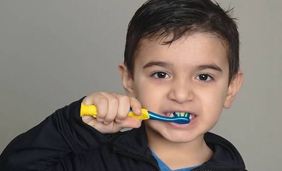 Child practicing tooth brushing with smile model